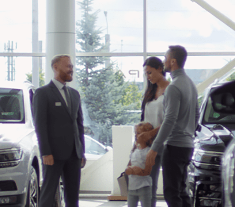 Family at a car dealership speaking with a salesperson