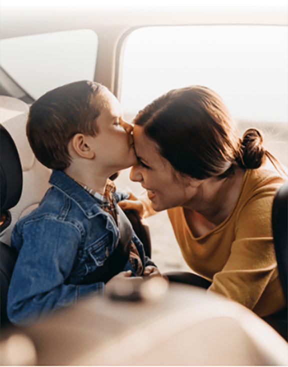 Toddler boy kissing his mother as she puts him into a child car seat