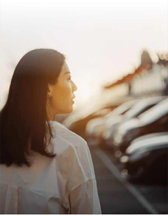 A young woman walking looking at the available cars at a dealership