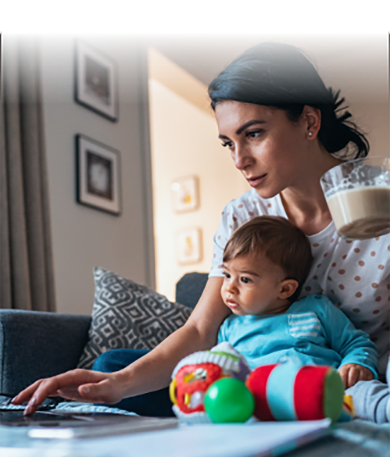 A woman holding an infant applying online for an Affinity Credit Card